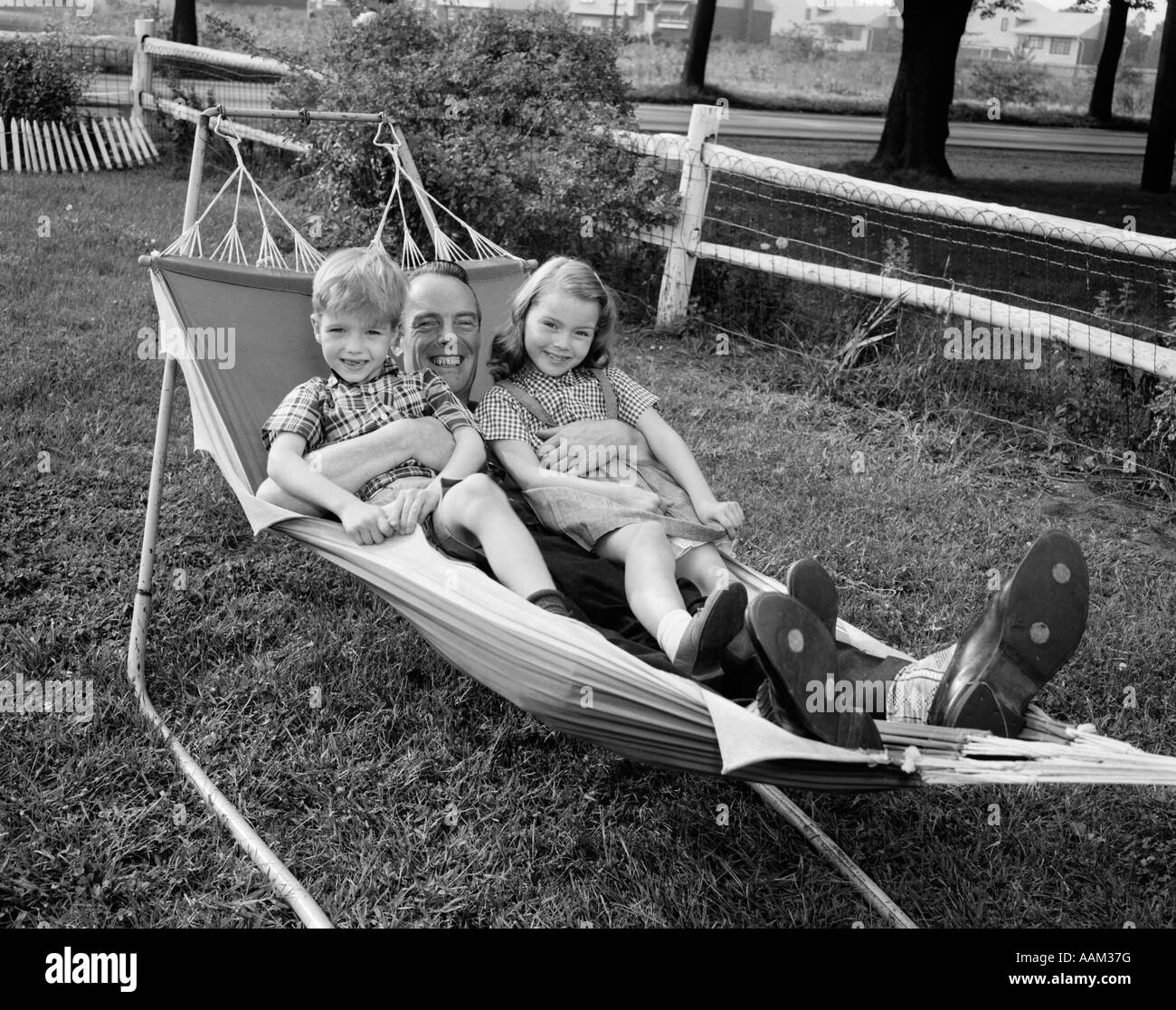 1950s FATHER LYING IN HAMMOCK HOLDING 2 SMILING CHILDREN BOY GIRL - Stock Image