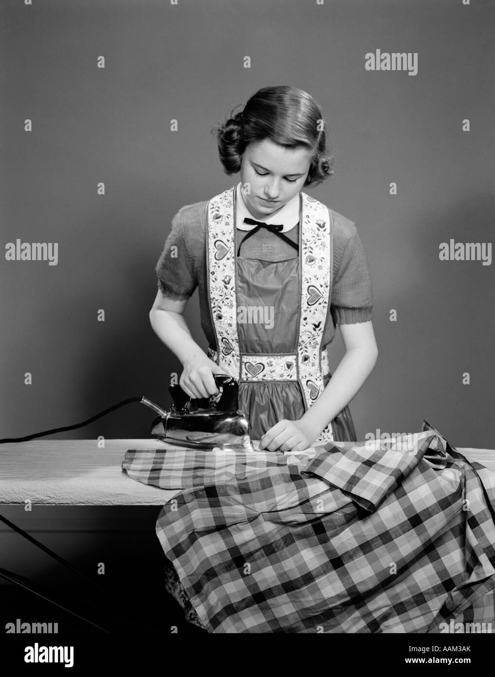 1950s Young Teen Girl Wearing Apron Ironing Shirt