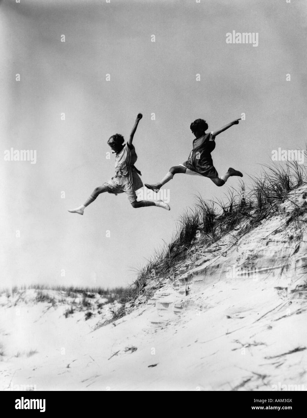 1920s 1930s TWO GIRLS MIDAIR JUMPING OFF OF BEACH SAND DUNE - Stock Image