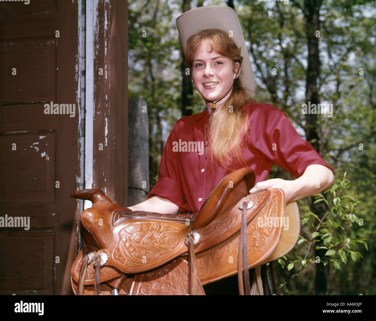 1960s TEEN GIRL RED SHIRT COWBOY HAT CARRYING WESTERN LEATHER SADDLE COWGIRL HORSEBACK RIDER - Stock Image