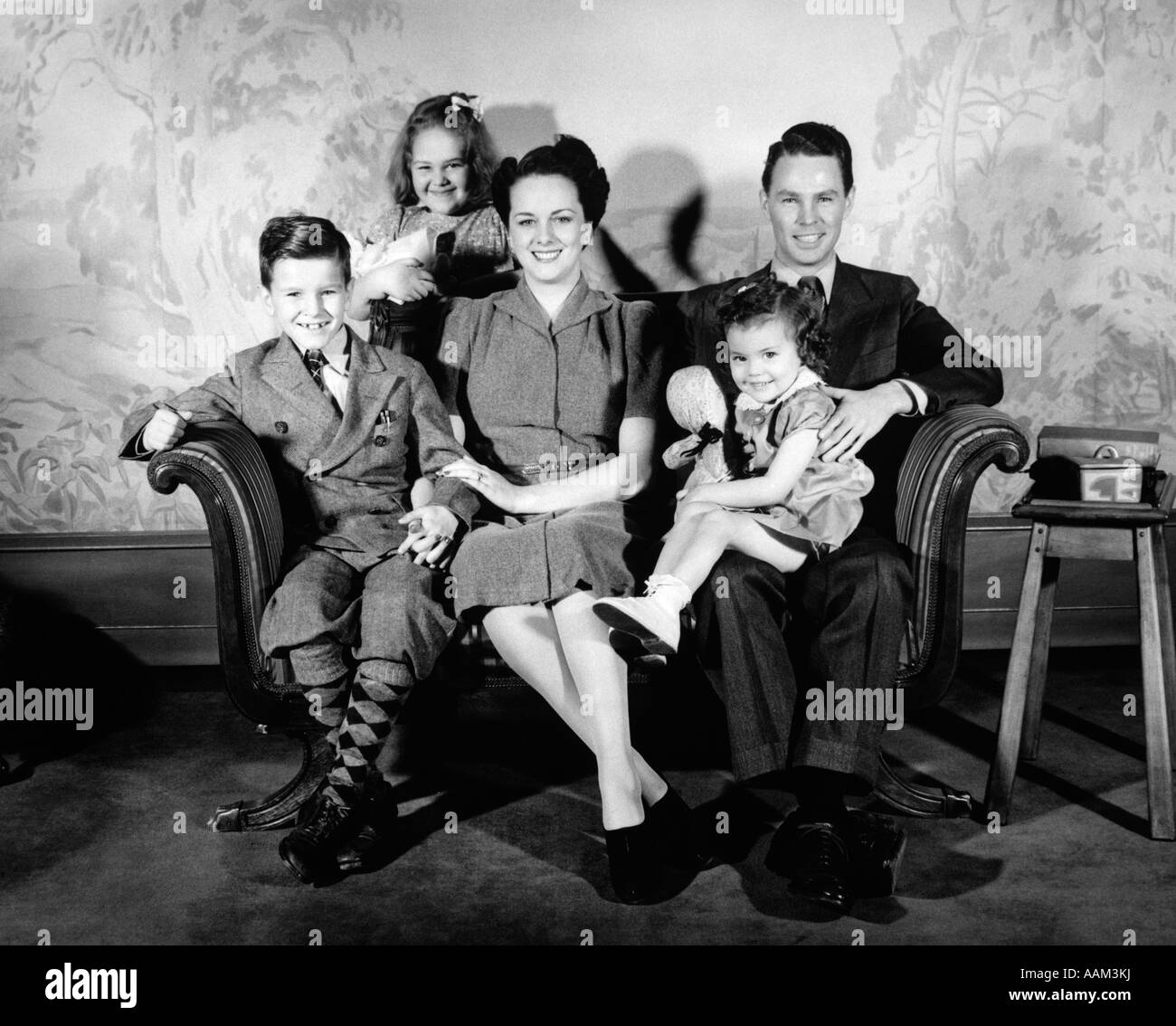 1940s FAMILY OF 5 PORTRAIT SITTING ON COUCH FACING CAMERA SMILING MOTHER FATHER TWO GIRLS ONE BOY WALLPAPER PRINT - Stock Image