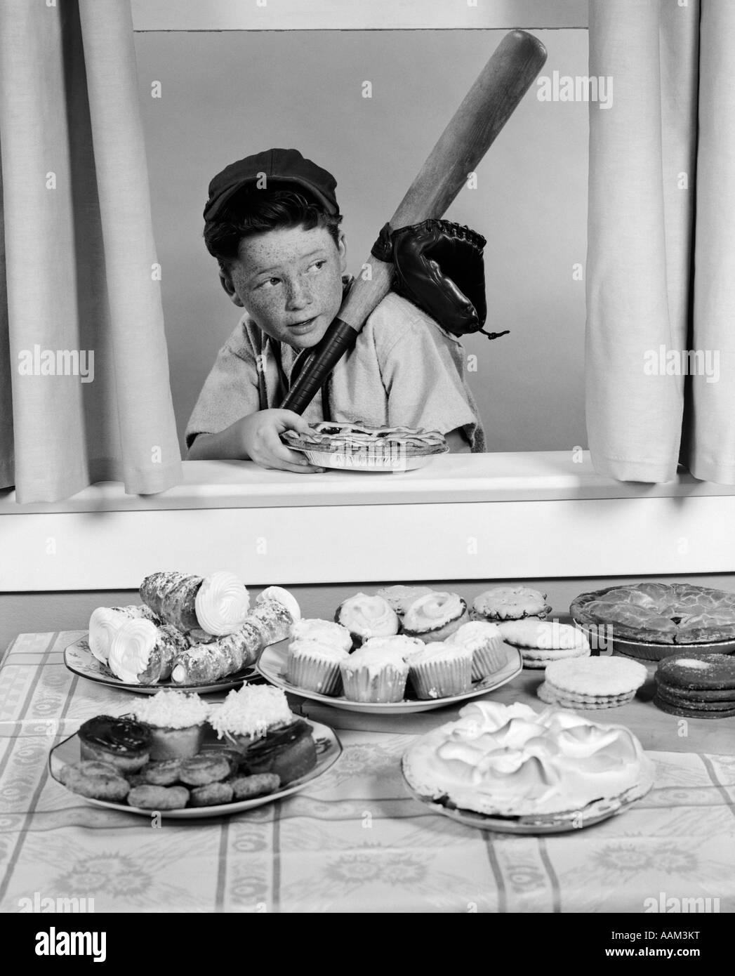 1950s BOY IN BASEBALL GARB WITH BAT SNEAKING PIE THROUGH OPEN WINDOW Stock Photo