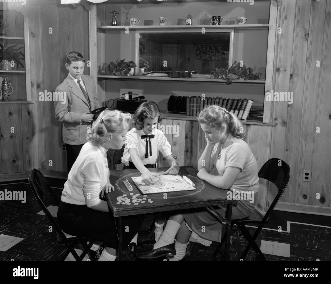 1950s GIRLS PLAYING SCRABBLE IN REC ROOM WITH BOY CHANGING RECORDS - Stock Image