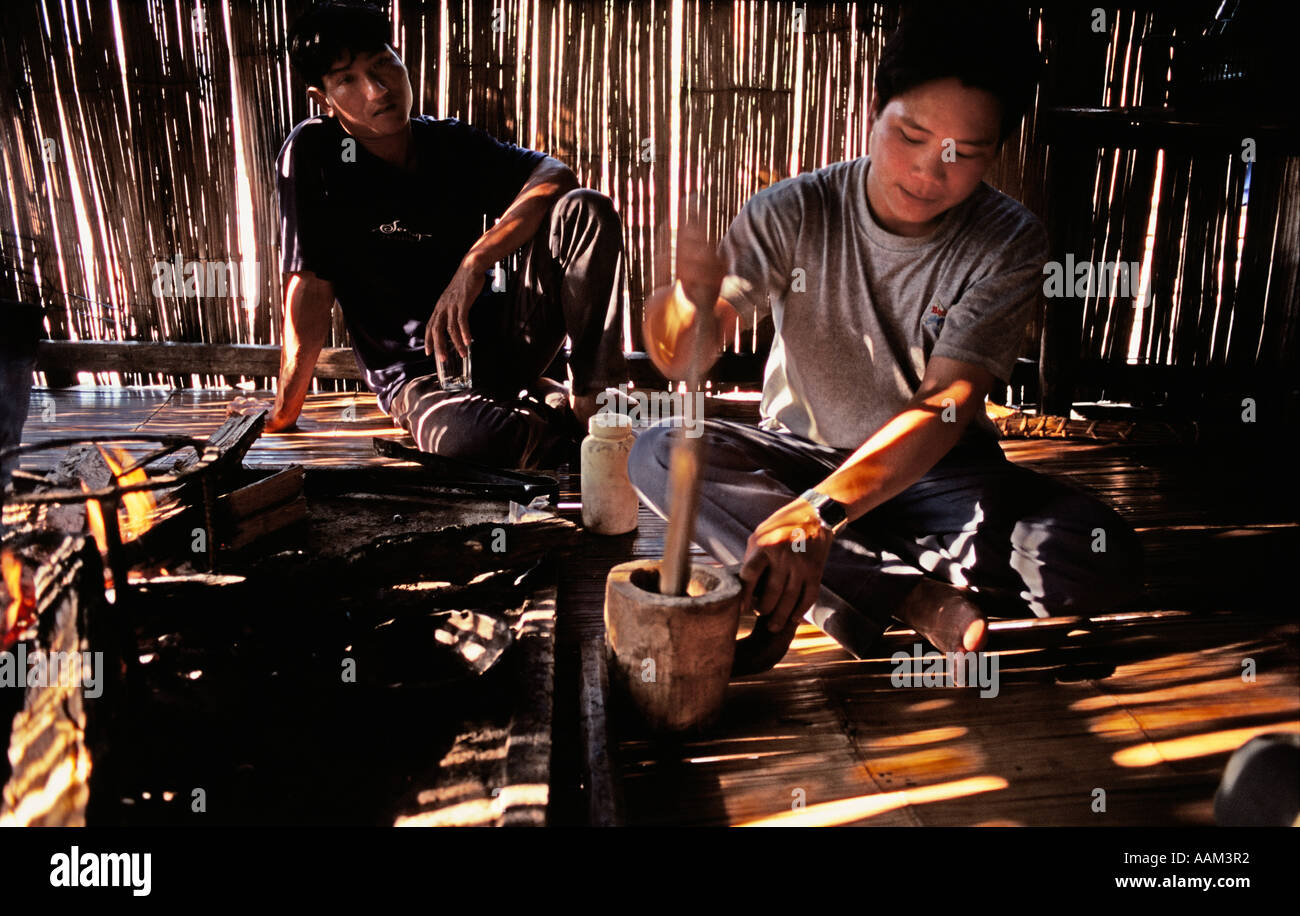 Lahu villager prepares meal by open fire in bamboo hut, northern Thailand - Stock Image