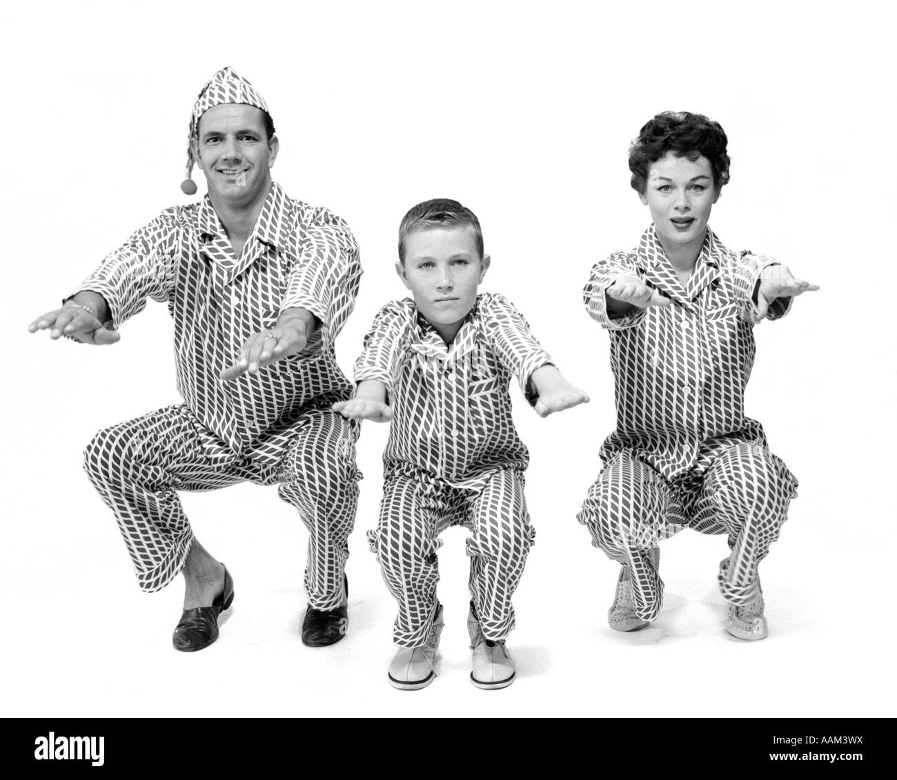 1950s FAMILY OF 3 IN PAJAMAS DOING KNEE BENDS FACING CAMERA - Stock Image