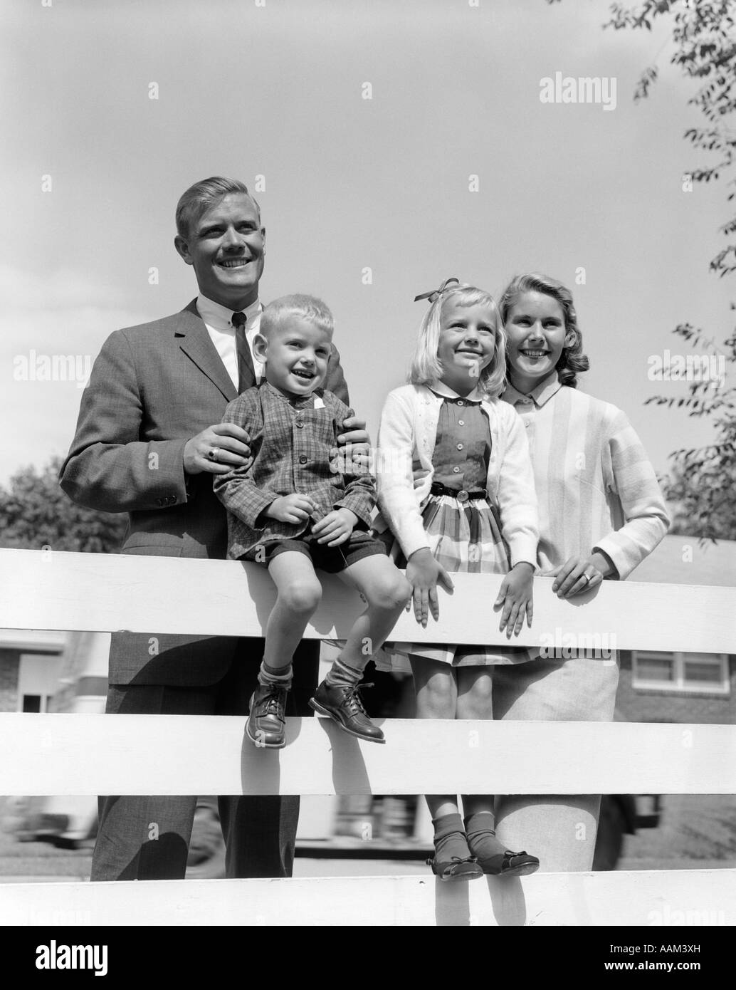 1950s FAMILY PORTRAIT FATHER MAN WOMAN MOTHER GIRL DAUGHTER BOY SON BEHIND BACKYARD FENCE SMILING TOWARDS CAMERA - Stock Image