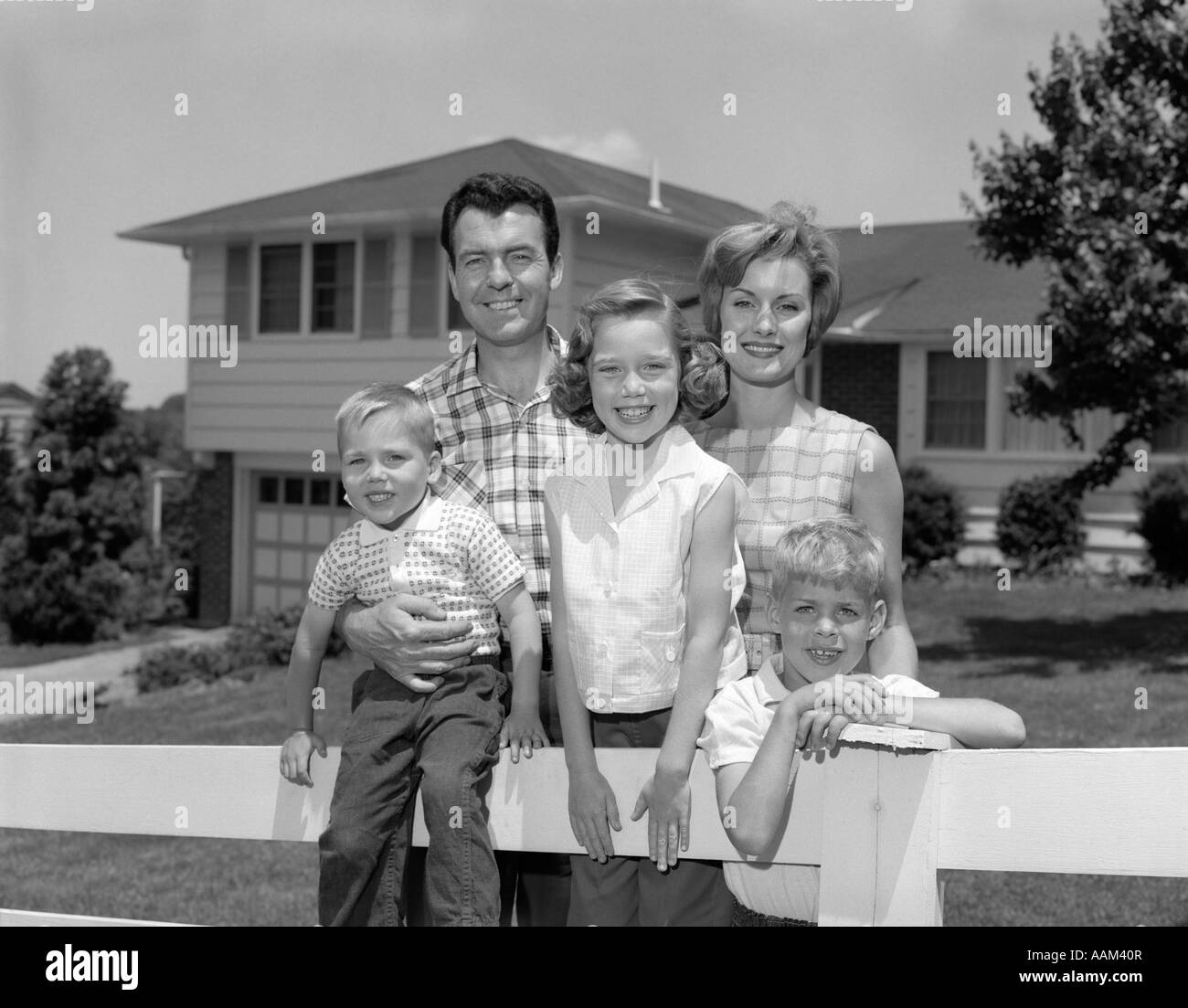 1960s FAMILY PORTRAIT IN FRONT OF HOUSE ON FENCE - Stock Image