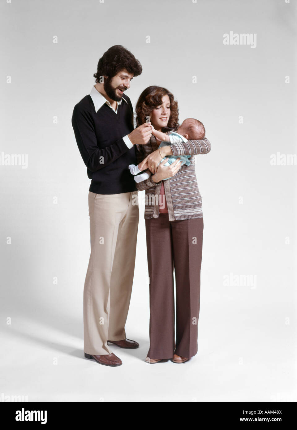 1970s FULL LENGTH PORTRAIT STANDING FAMILY 3 MOTHER FATHER BABY MAN WOMAN CHILD - Stock Image