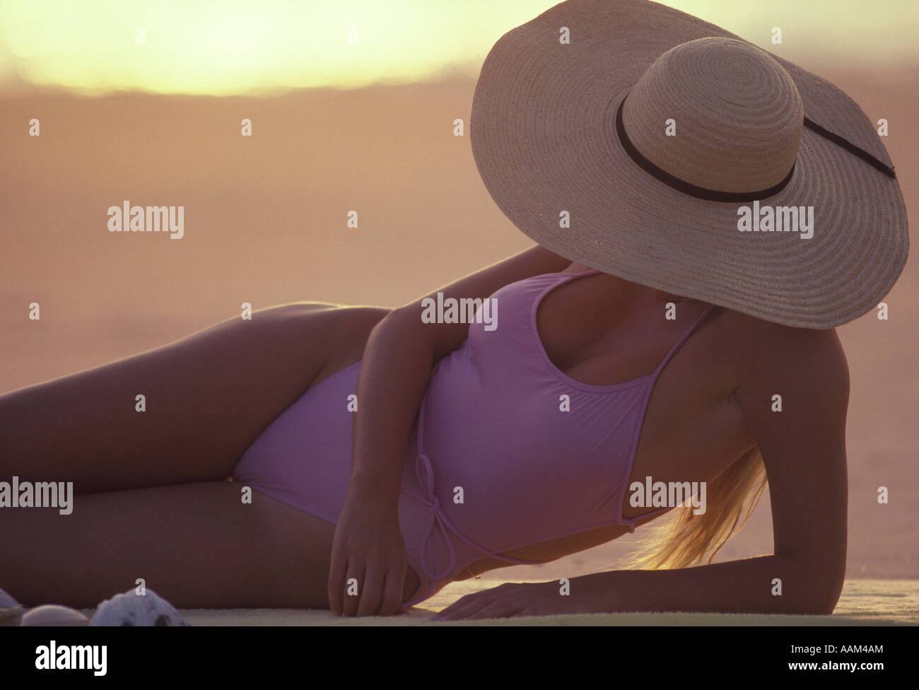 1980s WOMAN SUNBATHING WEARING LARGE STRAW HAT - Stock Image