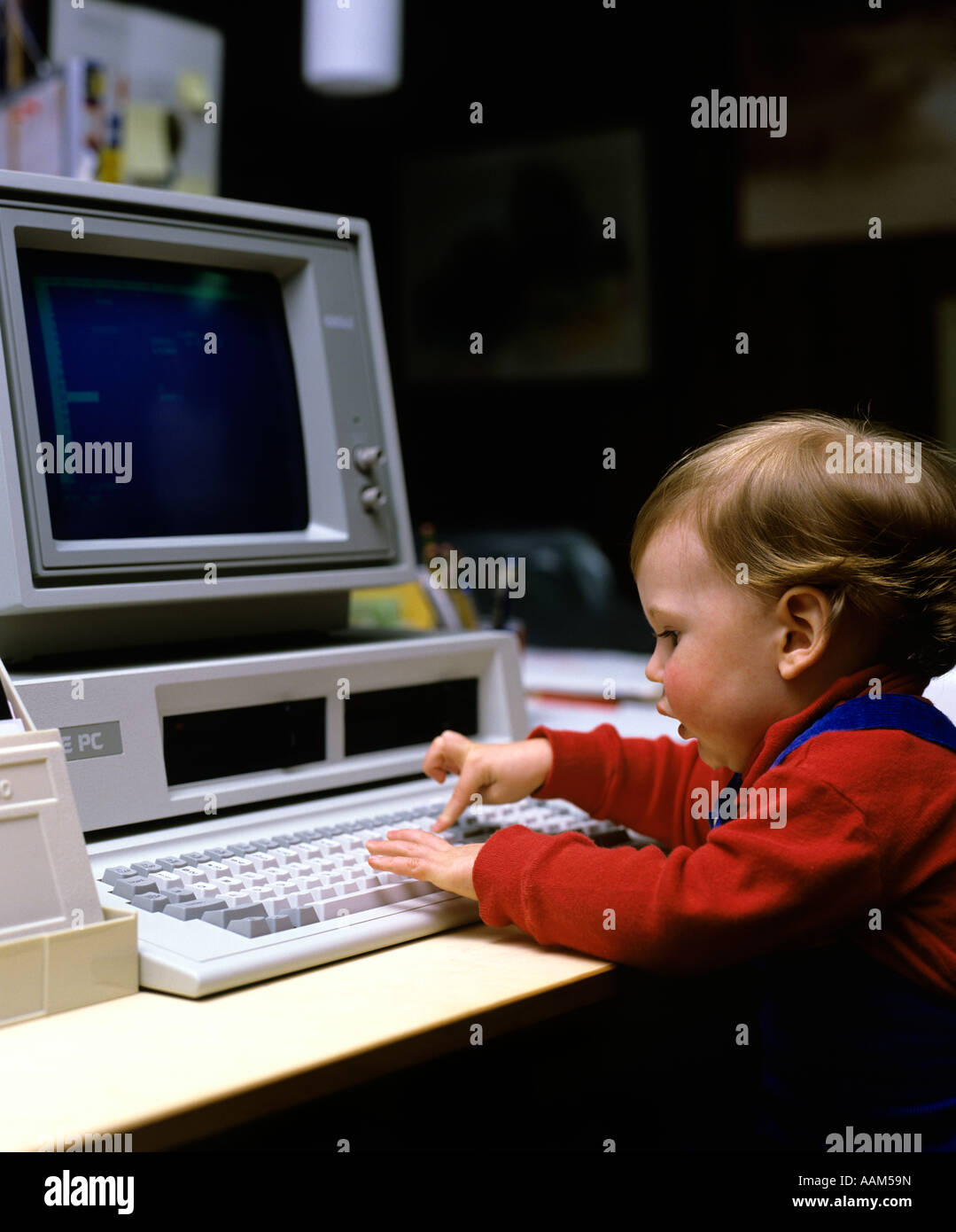 1980s YOUNG CHILD BOY GIRL PLAYING WITH EARLY IBM PC COMPUTER PRESSING KEY ON KEYBOARD Stock Photo