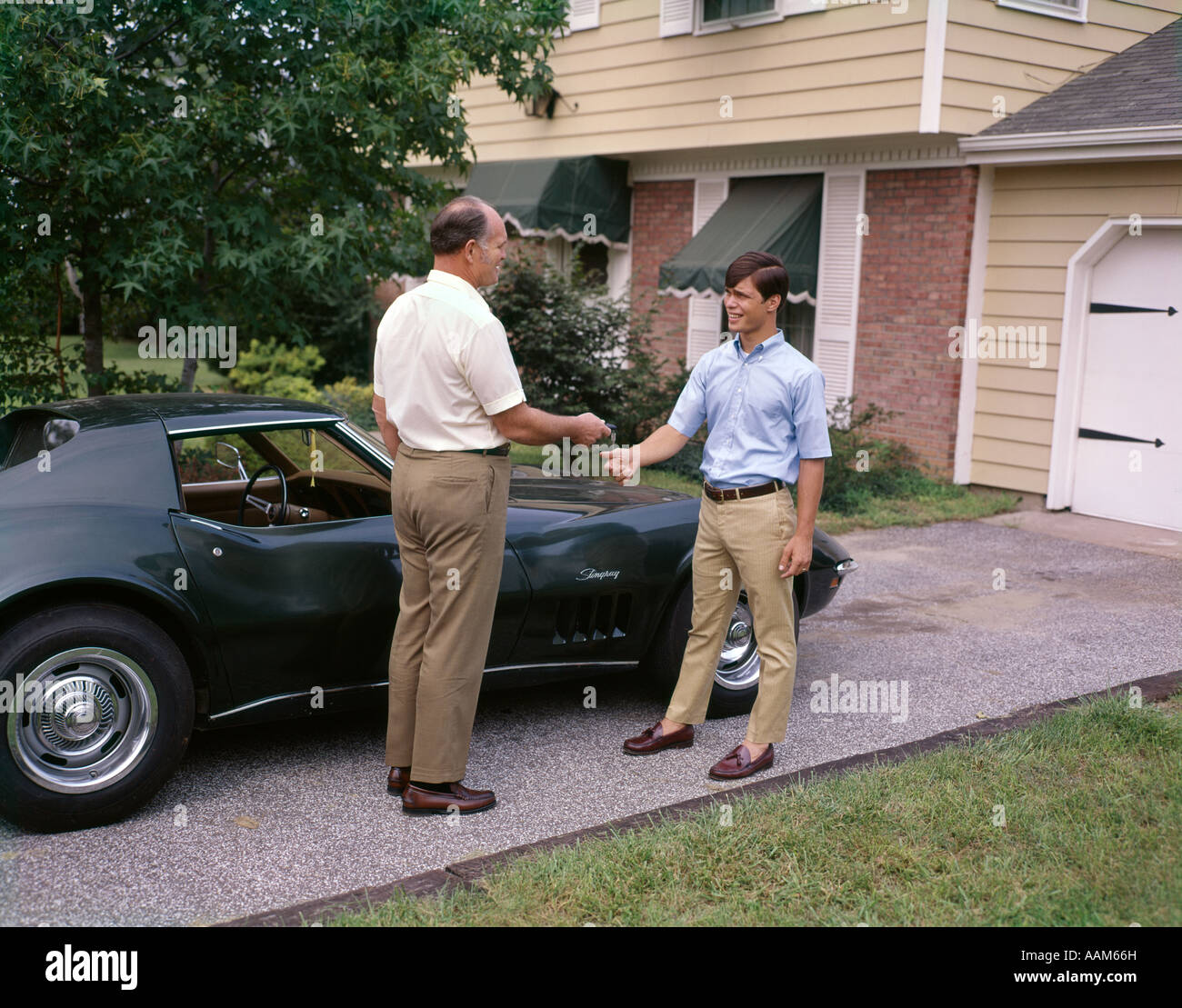 1970s FATHER HANDING TEENAGE SON KEYS TO FAMILY CAR MAN