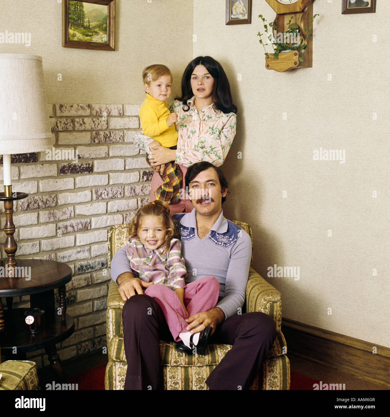 1970s FAMILY PORTRAIT LIVING ROOM MAN FATHER SITTING CHAIR WOMAN MOTHER STANDING TWO KIDS FASHION CLOTHES - Stock Image