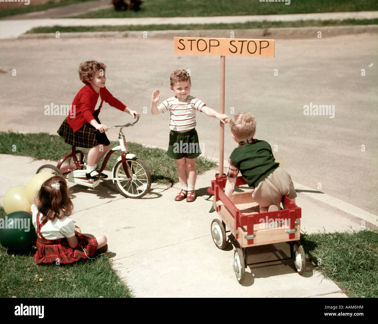 1950s BOYS AND GIRLS OUTDOOR WITH TRICYCLE AND WAGON PLAYING TRAFFIC WITH POLICE STOP SIGN AMERICANA NOSTALGIA - Stock Image
