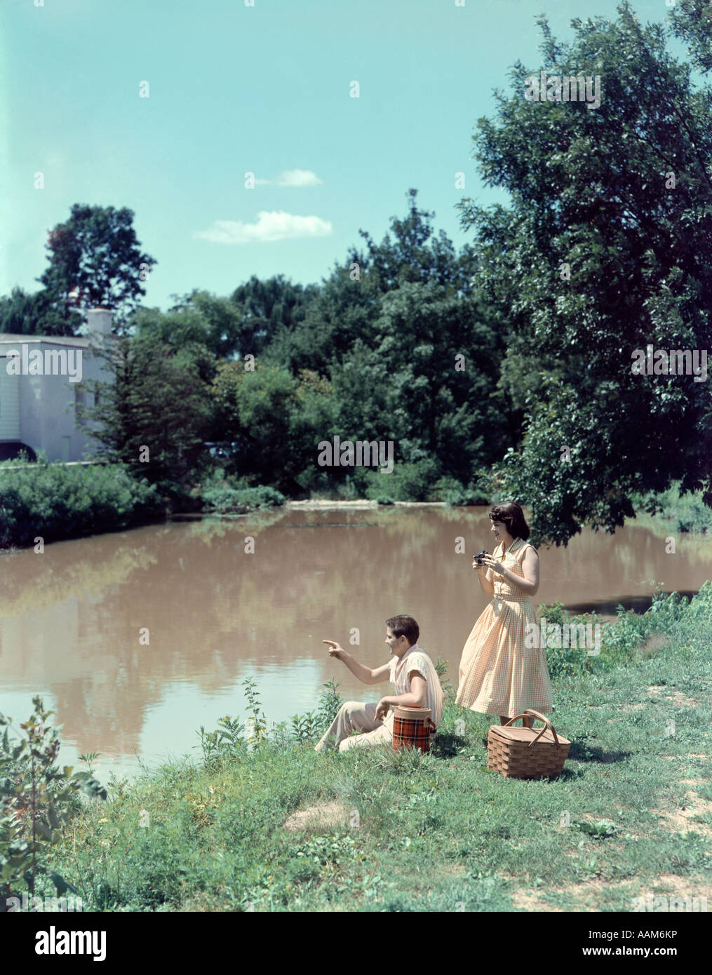 1950 1950s TEEN COUPLE BOY GIRL PICNIC BASKET ON BANK OF STREAM SUMMER DAY DATE CAMERA RETRO - Stock Image