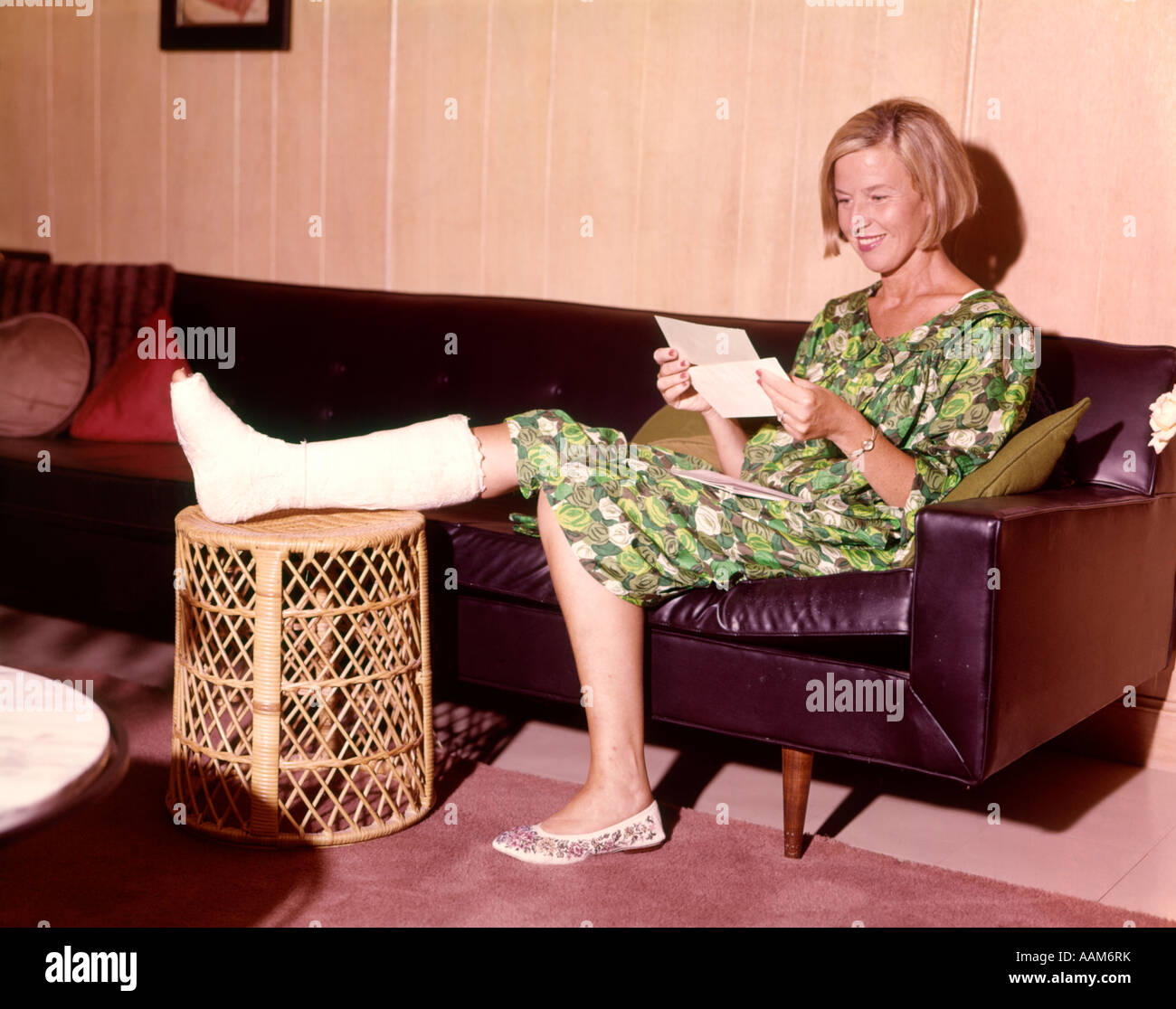 1960 1960s SMILING WOMAN LEG BROKEN IN CAST ON STOOL SITTING LEATHER SOFA OPENING INSURANCE CHECK - Stock Image