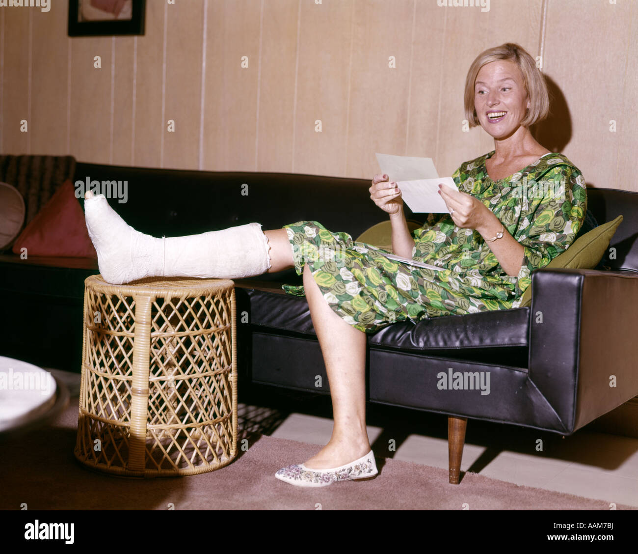 1960s WOMAN WITH BROKEN LEG IN CAST PROPPED ON HAMPER LOOKING AT LETTER HAPPY INSURANCE PAYMENT BASKET SMILING - Stock Image