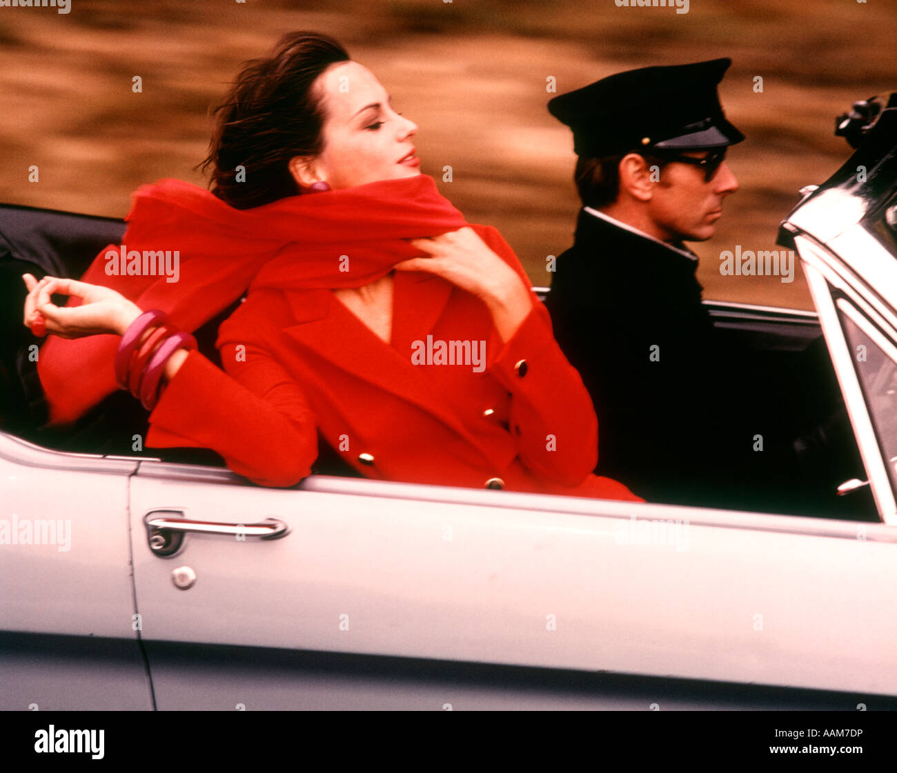 1970 1970s STYLISH WOMAN RED DRESS SCARF DRIVING OPEN AIR CONVERTIBLE SPORTS CAR CHAUFFEUR STYLE FASHION WEALTH - Stock Image