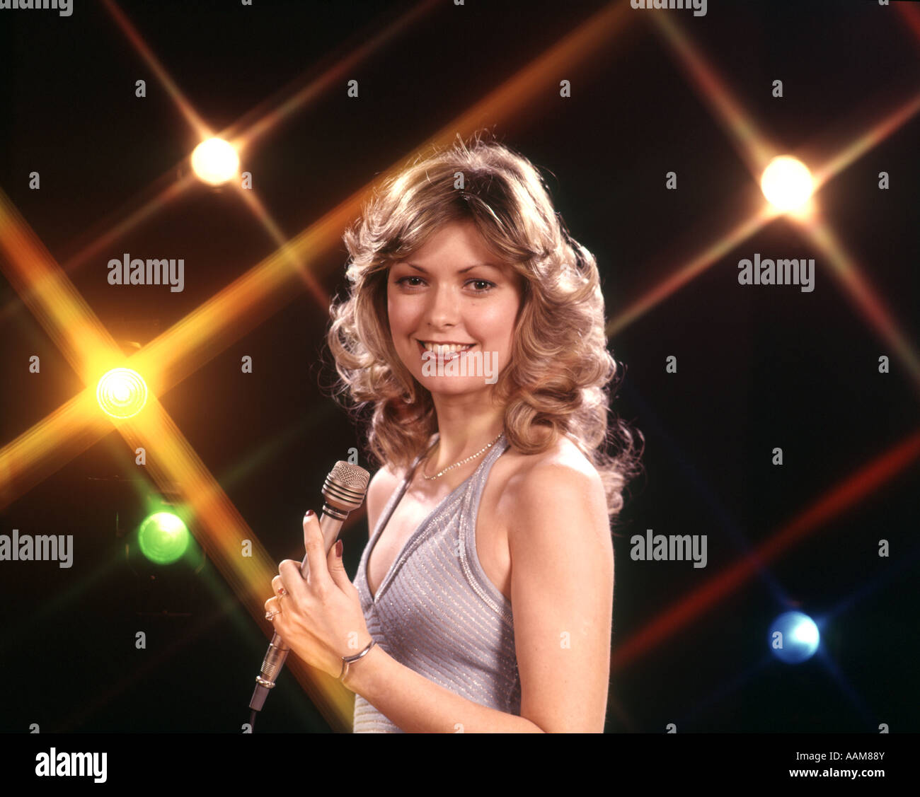1970 1970s FEMALE VOCALIST SINGER HOLD MICROPHONE STAGE LIGHTS BACKGROUND SING SINGER SINGING PERFORMER WOMAN WOMEN - Stock Image