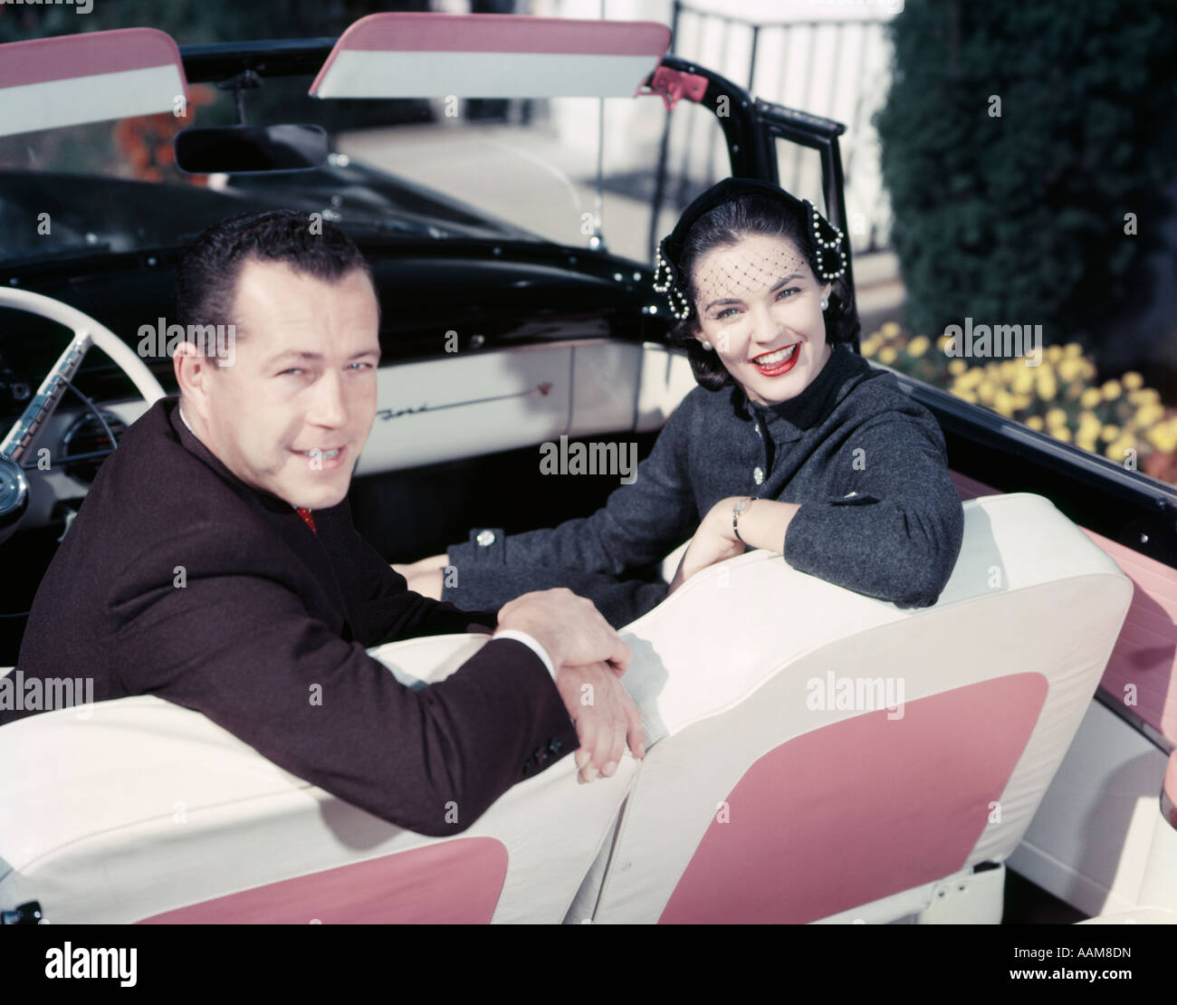 1950s SMILING COUPLE MAN WOMAN IN FRONT SEAT TURNED LOOK BACK CONVERTIBLE PINK WHITE UPHOLSTERY