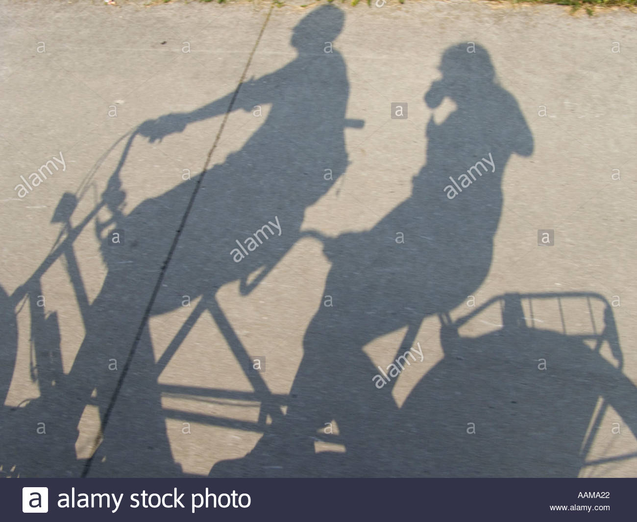 shadow of tandem bicycle with two people on it - Stock Image