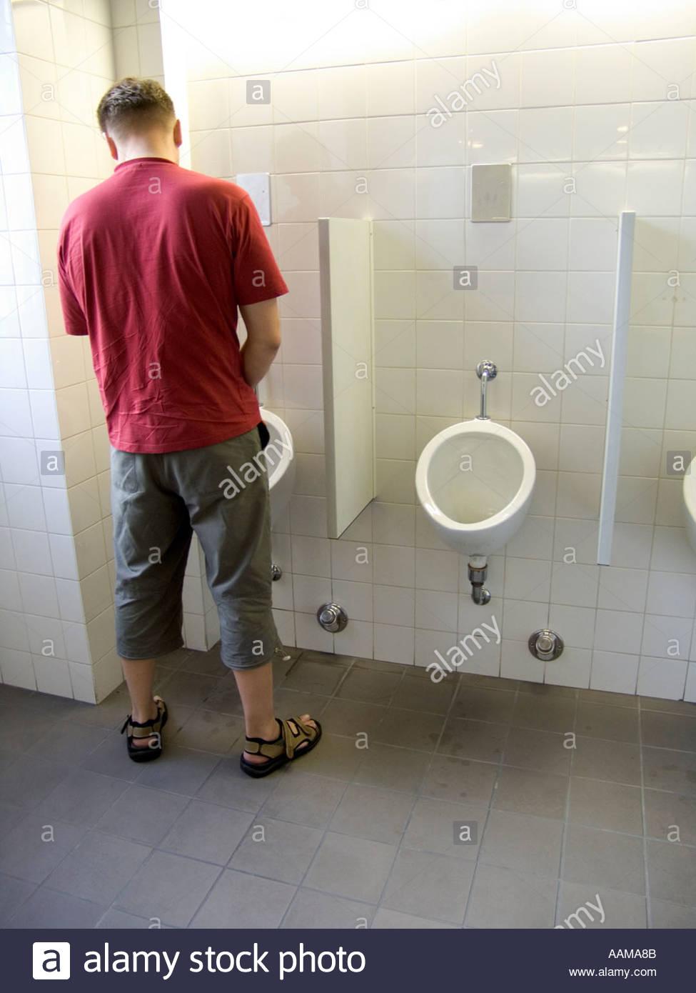 Man Using A Urinal In Mens Public Lavatory