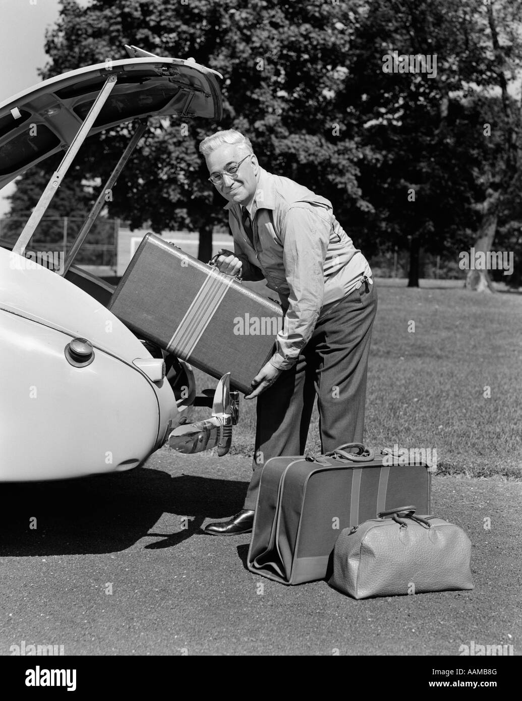 1940s MAN PACKING CAR TRUNK LUGGAGE TRIP ELDERLY - Stock Image