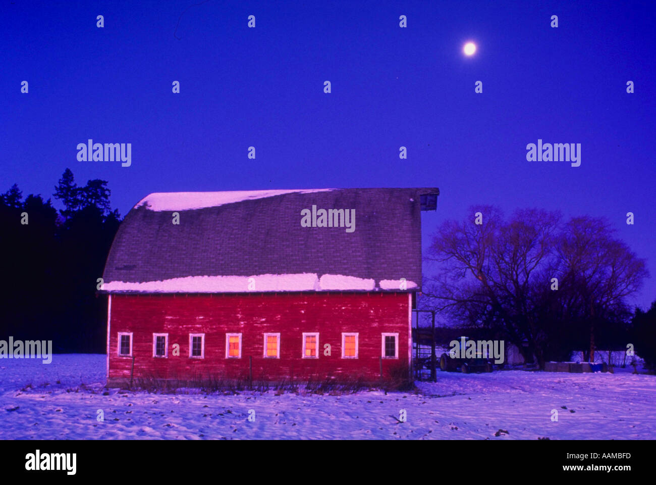 Moonrise over red barn in snowy field Skagit Valley NW Washington - Stock Image