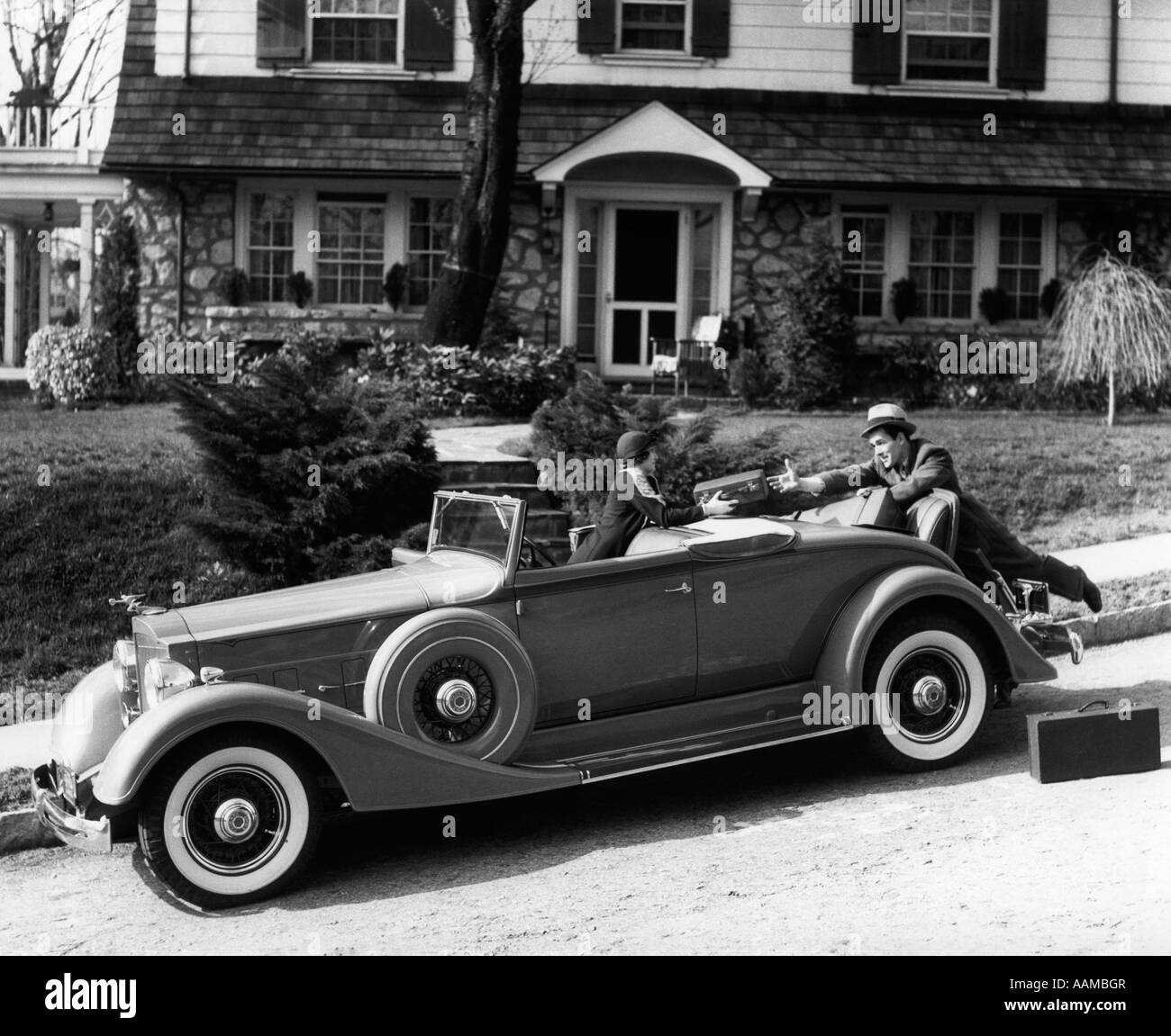 1930s WOMAN IN CAR PACKARD HANDING SUITCASE TO MAN IN FRONT OF HOUSE COUPLE TRAVEL TRIP - Stock Image
