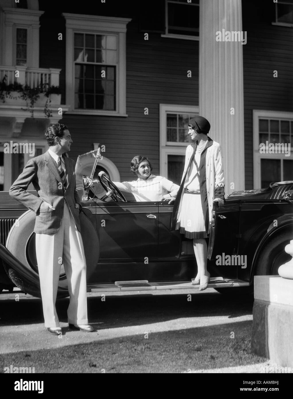 1930s MAN AND TWO WOMEN IN STYLISH CLOTHES WITH TOURING CAR PARKED IN FRONT OF ELEGANT LARGE HOUSE - Stock Image
