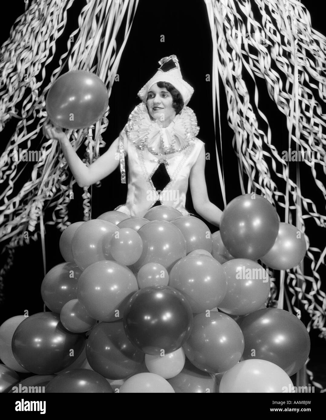 1920s 1930s SMILING YOUNG WOMAN Pierrot CLOWN AMID PARTY BALLOONS AND PAPER STREAMERS - Stock Image