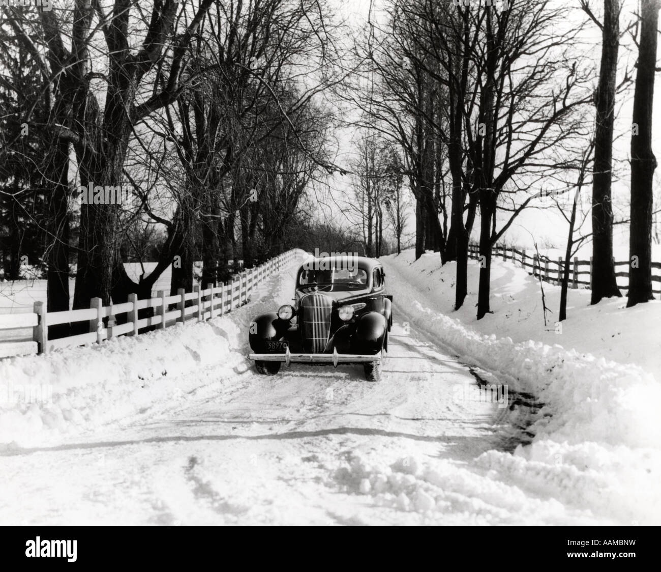 1930s CAR DRIVING DOWN SNOWY COUNTRY ROAD - Stock Image