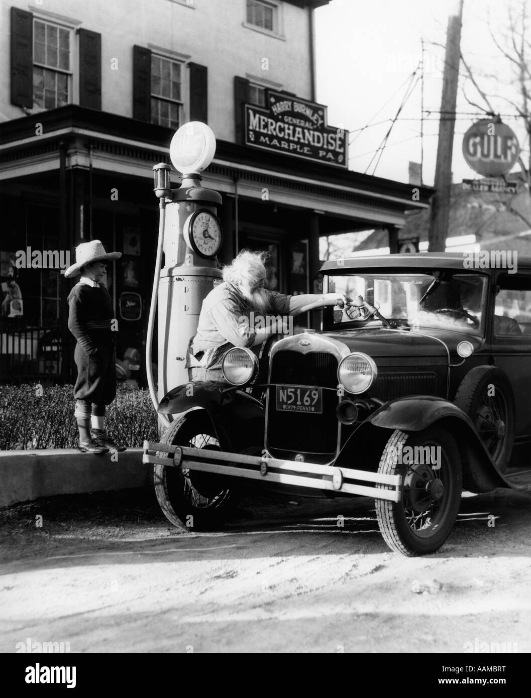 ELDERLY GRANDFATHER FILLING UP FORD CAR IN FRONT OF PENNSYLVANIA GENERAL STORE WITH GRANDSON WATCHING 1930s - Stock Image