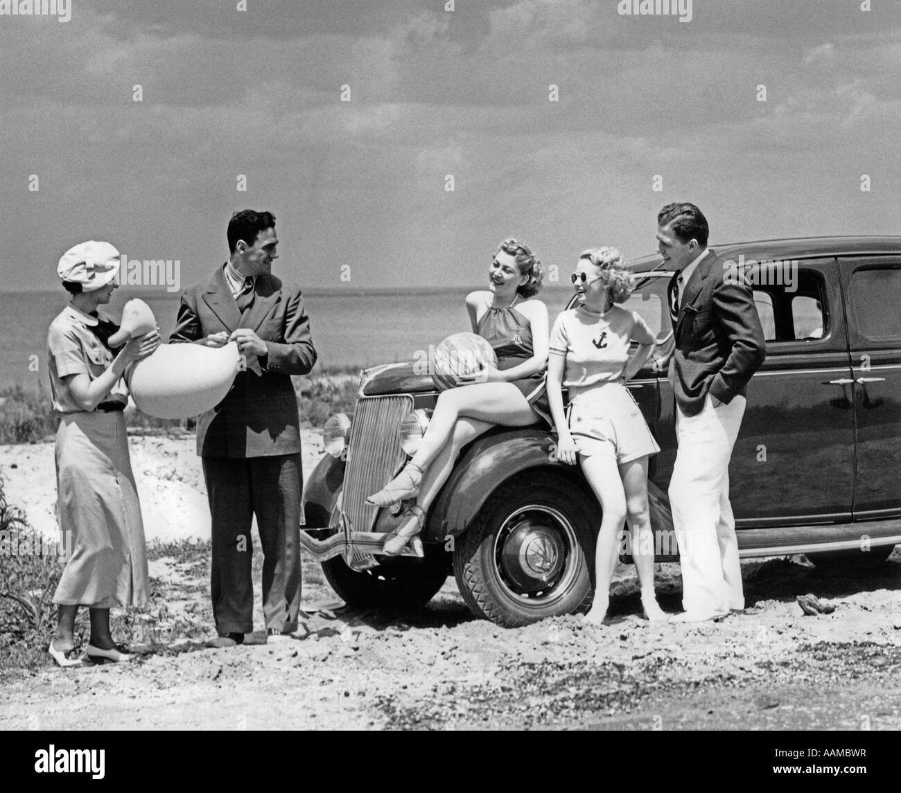 1930s GROUP OF FIVE MEN & WOMEN AT 1936 FORD V-8 PARKED ALONG SHORE PLAYING WITH INFLATABLE BEACH TOYS - Stock Image
