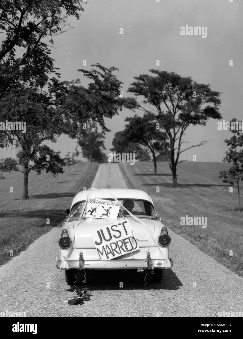1950s BACK OF WHITE FORD SEDAN DRIVING OFF WITH JUST MARRIED SIGN ON TRUNK - Stock Image