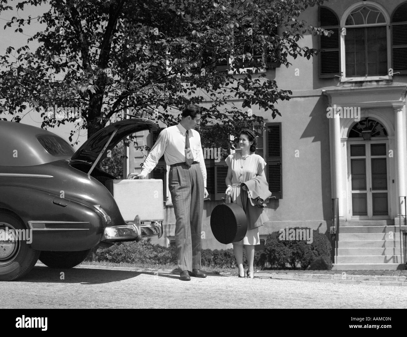 1940s MAN WOMAN LOADING TRUNK OF CAR WITH SUITCASES LUGGAGE IN FRONT OF HOUSE - Stock Image