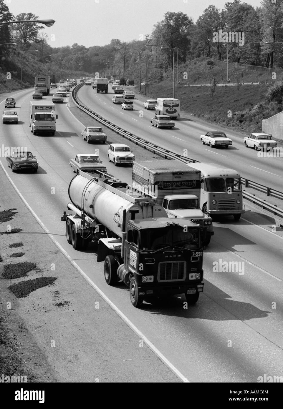 1960s TANKER TRUCK TRAVELING ON BUSY EXPRESSWAY - Stock Image