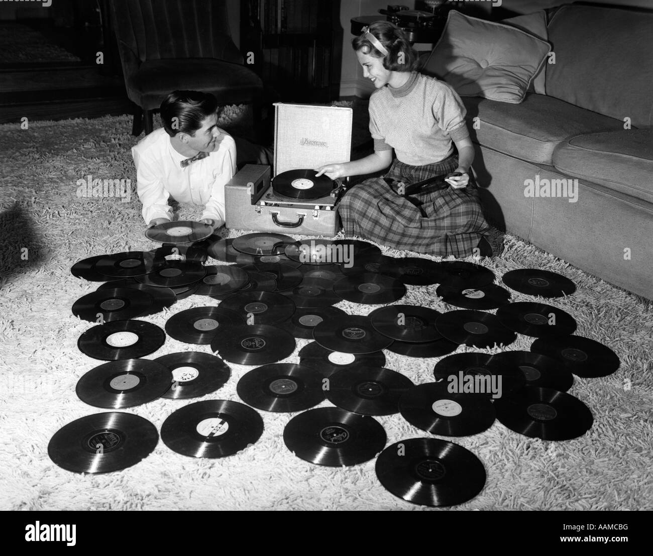 1950s TEENAGE COUPLE PLAYING MANY MUSIC RECORDS SPREAD OUT ON LIVING ROOM FLOOR - Stock Image