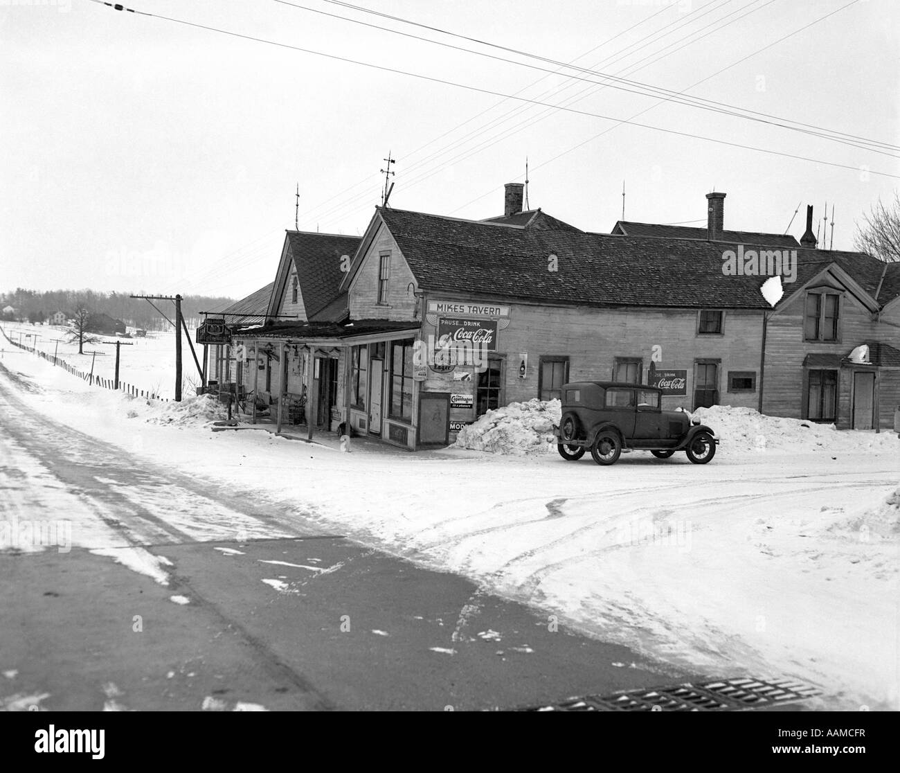 1910s 1920s CAR PARKED BESIDE ROADSIDE TAVERN IN SNOW - Stock Image