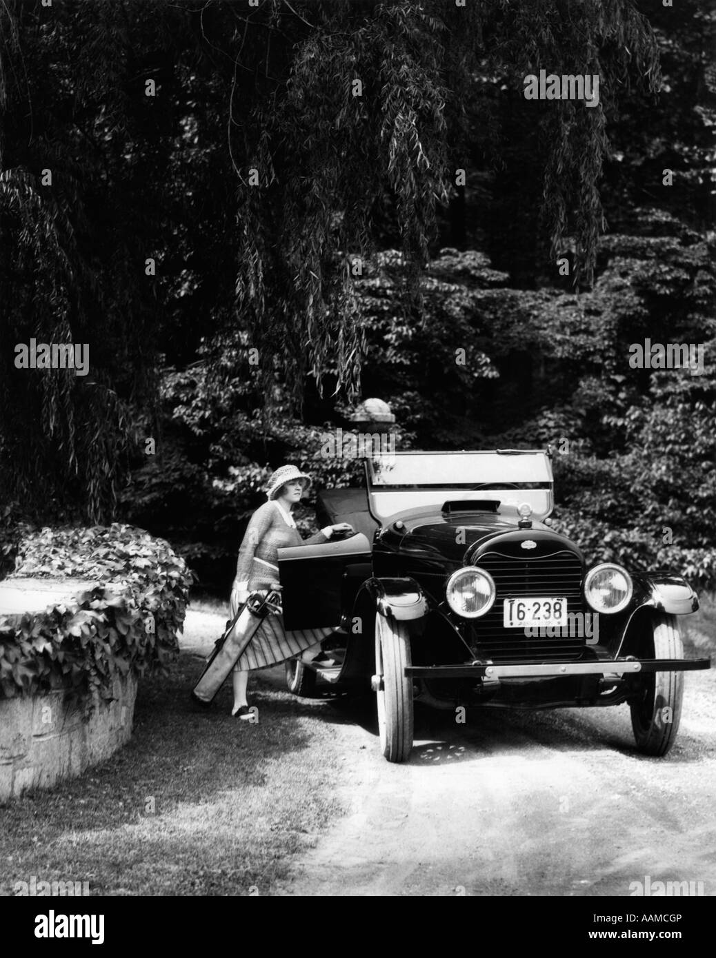 1920s WOMAN GETTING INTO PASSENGER SIDE OF CAR CARRYING GOLF BAG IN WOODED AREA - Stock Image