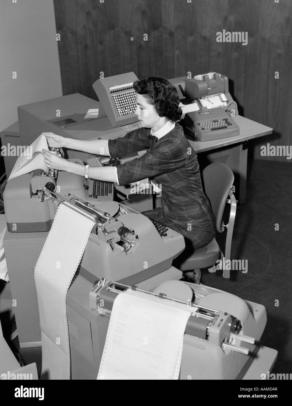 1950s WOMAN AT WORK STATION SURROUNDED BY ACCOUNTING MACHINES SPEWING OUT PAPER - Stock Image
