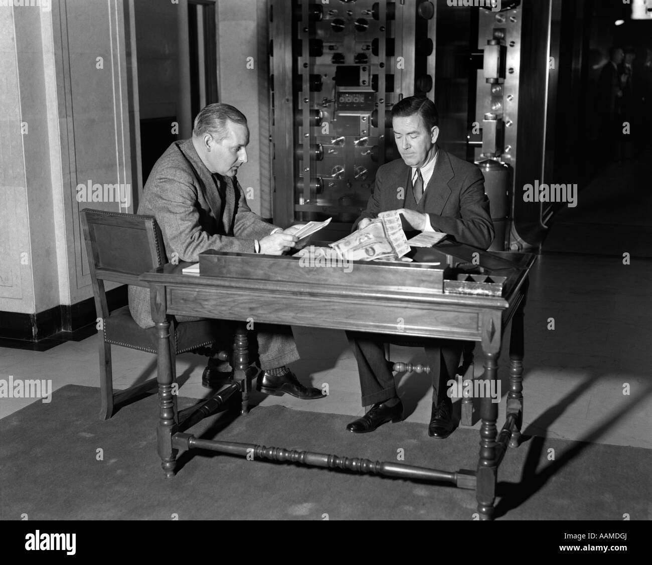 1930s TWO MEN SEATED AT TABLE BEFORE BANK VAULT SAFE DEPOSIT BOX CLIPPING COUPONS FINANCE SECURITY - Stock Image