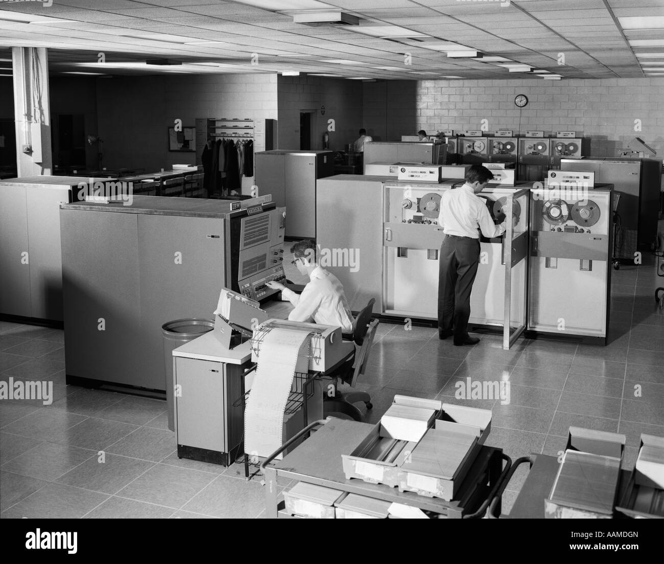1960s TWO MEN TECHNICIANS WORKING IN IBM 360 MAINFRAME