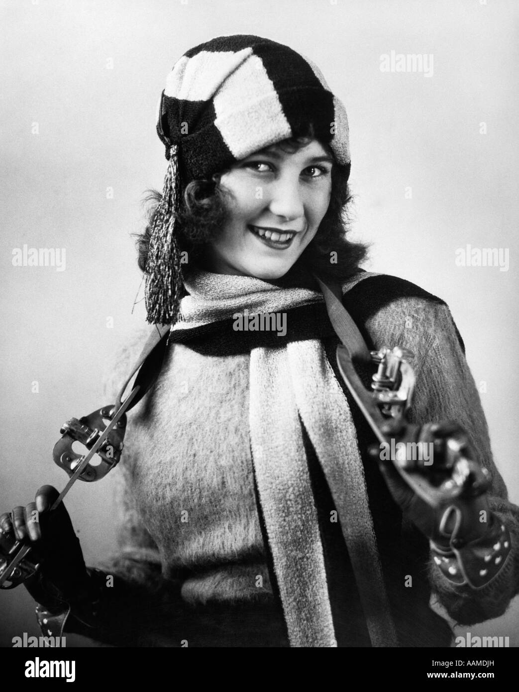 1920s WOMAN WEARING SWEATER SCARF & HAT WITH STRAP-ON ICE SKATES HANGING AROUND NECK - Stock Image