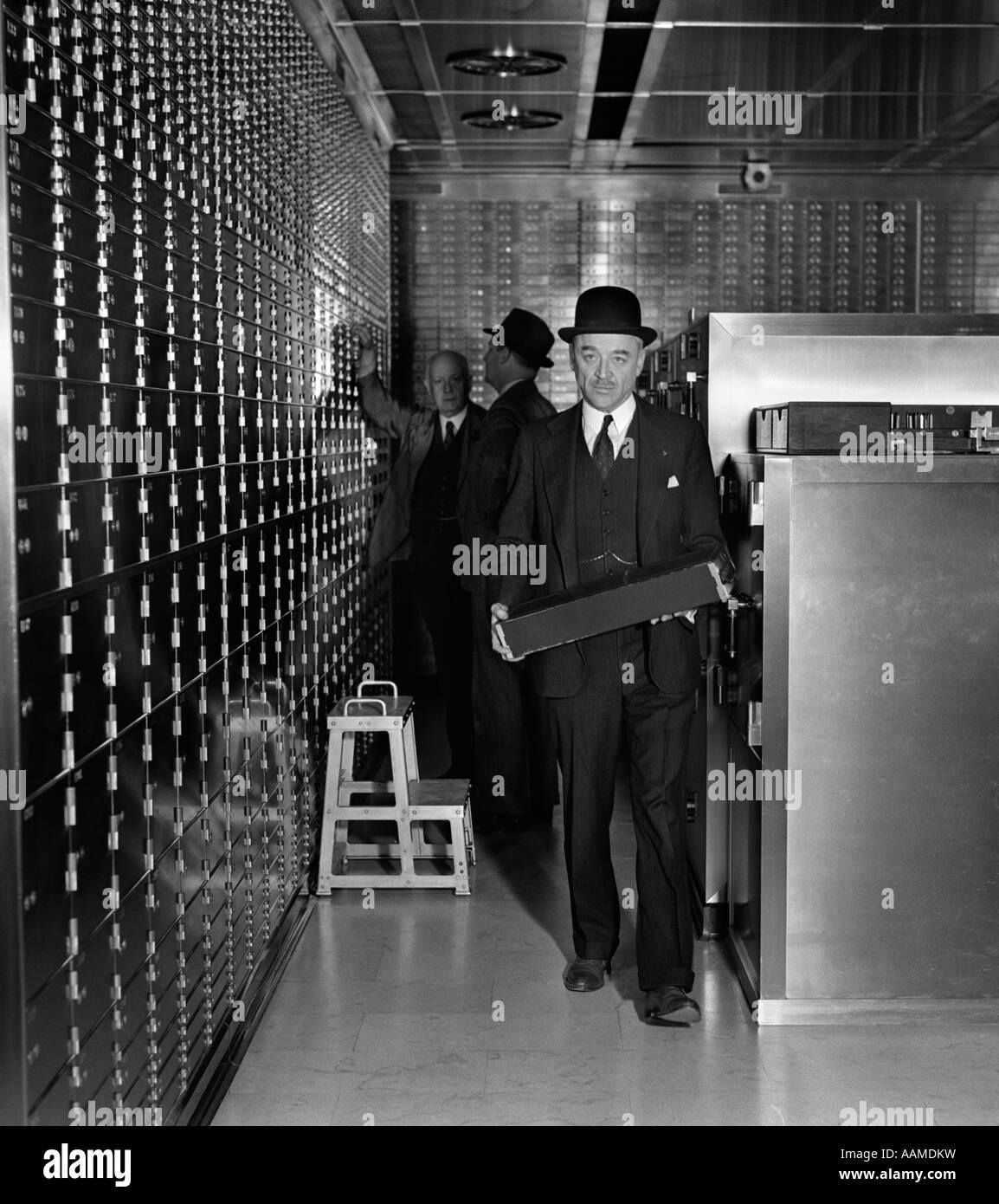 MEN MAN CARRY CARRYING SAFETY DEPOSIT BOX WEAR HAT SUIT VAULT 1930s INSPECT BANK VALUABLE - Stock Image