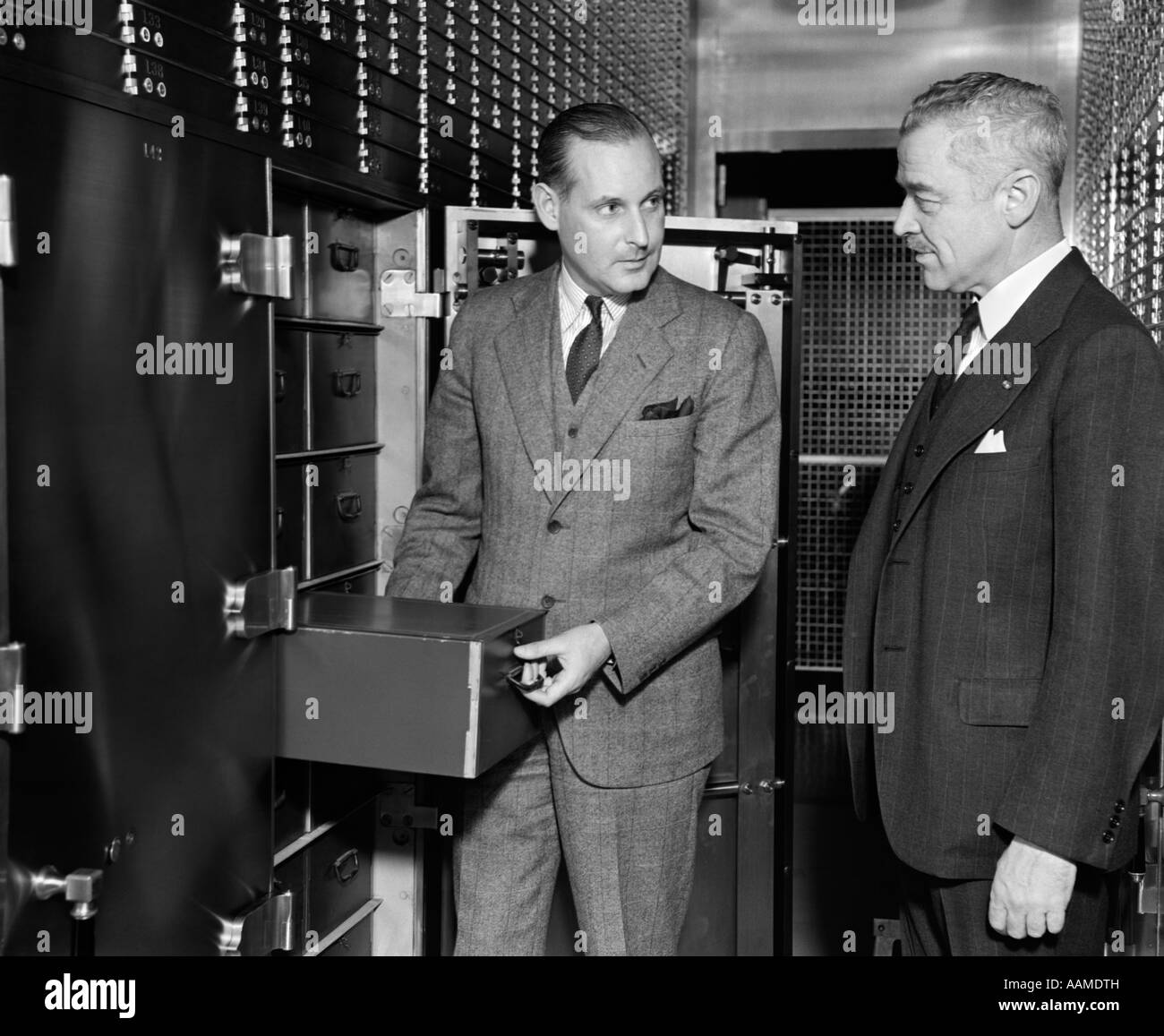 1940s TWO MEN BANK OPEN SAFETY DEPOSIT BOX VIEW VAULT SAVINGS BANK SECURITY VALUABLES RETRO VINTAGE - Stock Image