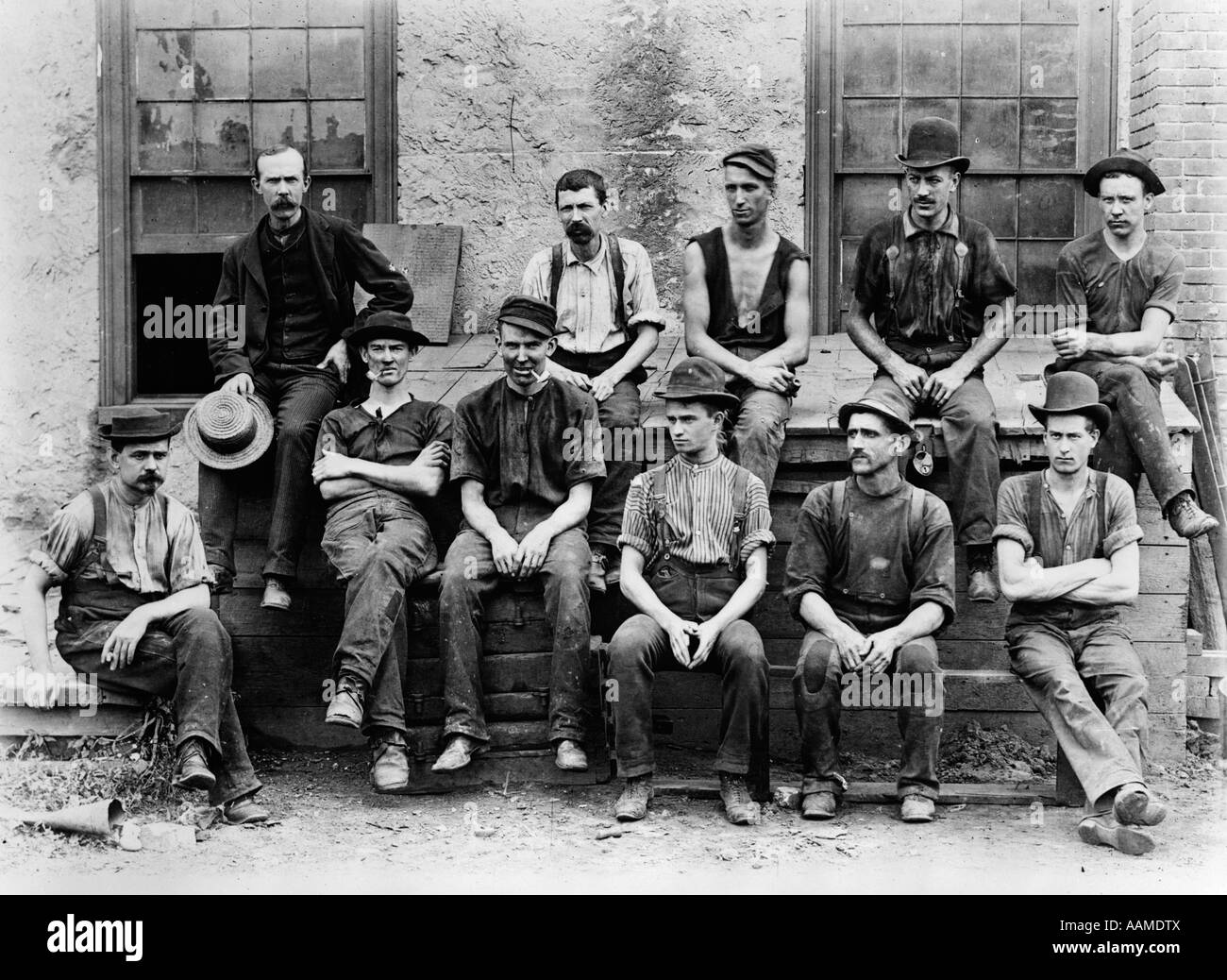 1890s 1900s GROUP OF 11 FACTORY WORKERS SEATED OUTSIDE OF BUILDING - Stock Image