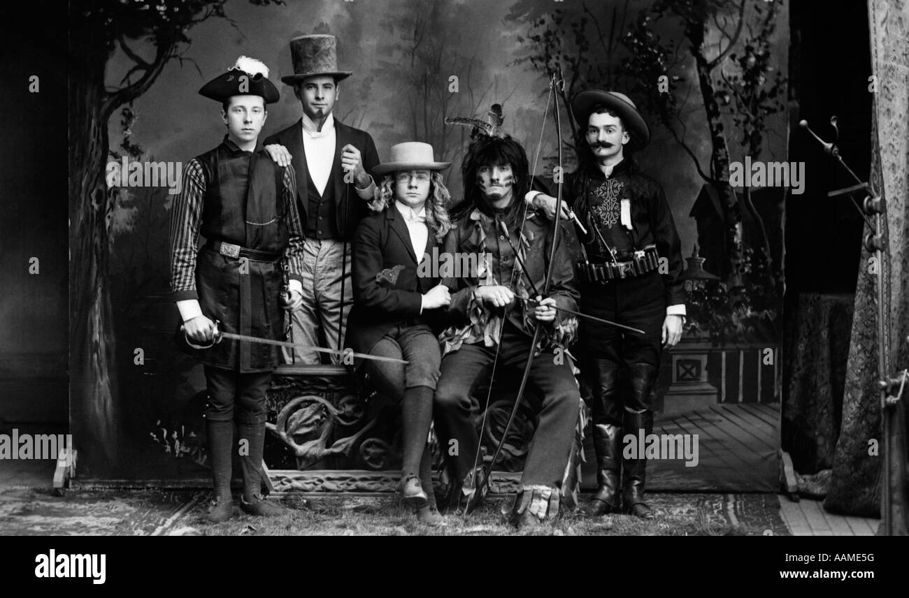 1890s TURN OF THE CENTURY PORTRAIT GROUP OF FIVE MEN ACTORS IN VARIOUS COSTUMES AGAINST PAINTED STUDIO BACKDROP - Stock Image