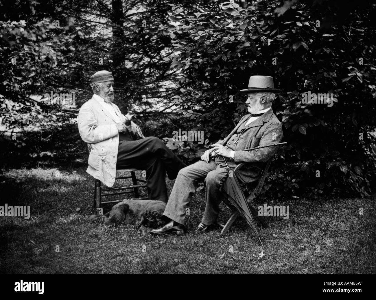 TURN OF THE CENTURY TWO MEN SITTING OUTSIDE IN CHAIRS AMONG TREES SMOKING CIGARS TALKING DOG LAYING AT THEIR FEET - Stock Image