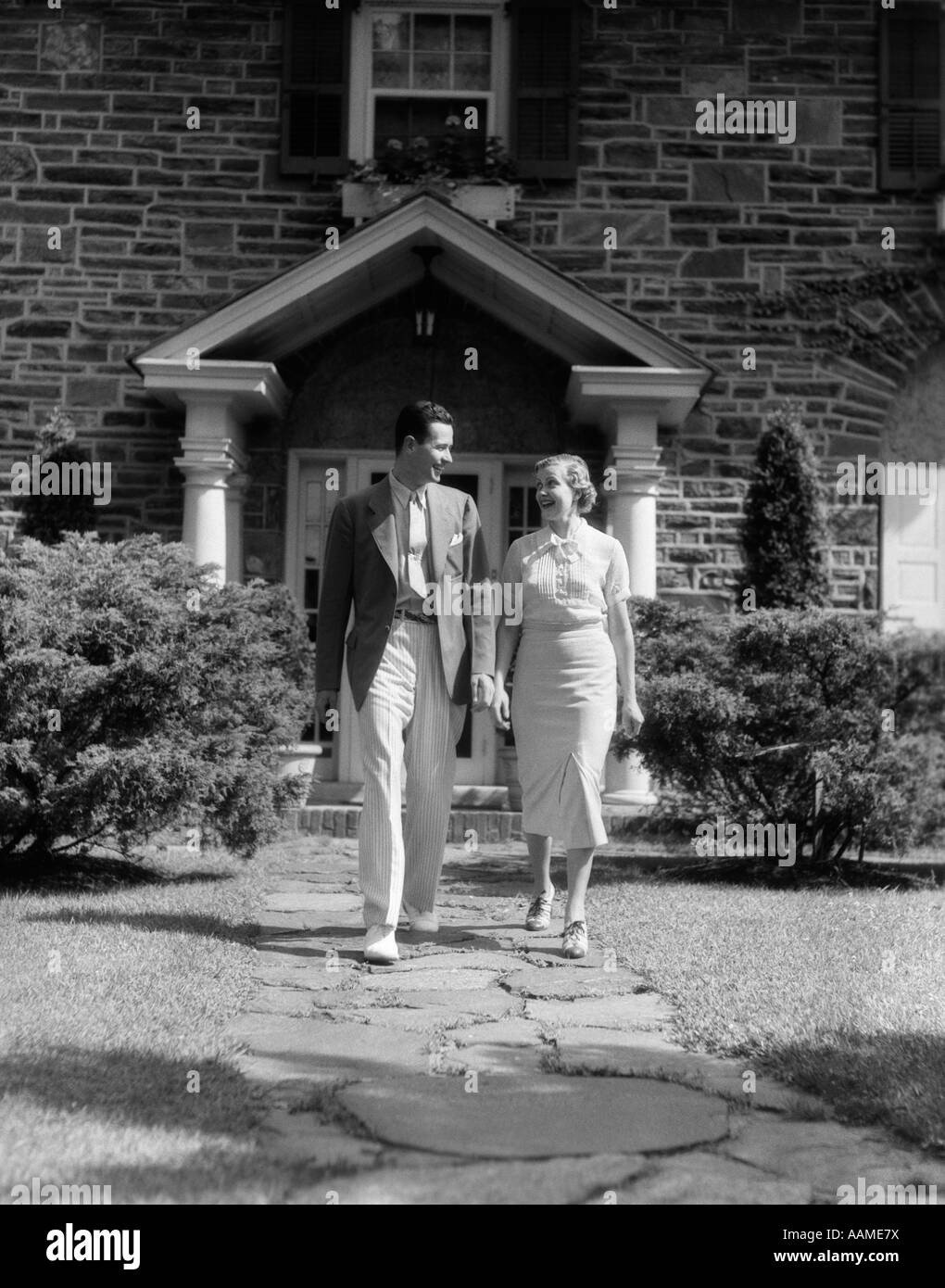 1930s COUPLE WALKING DOWN SIDEWALK IN FRONT OF HOUSE TALKING - Stock Image