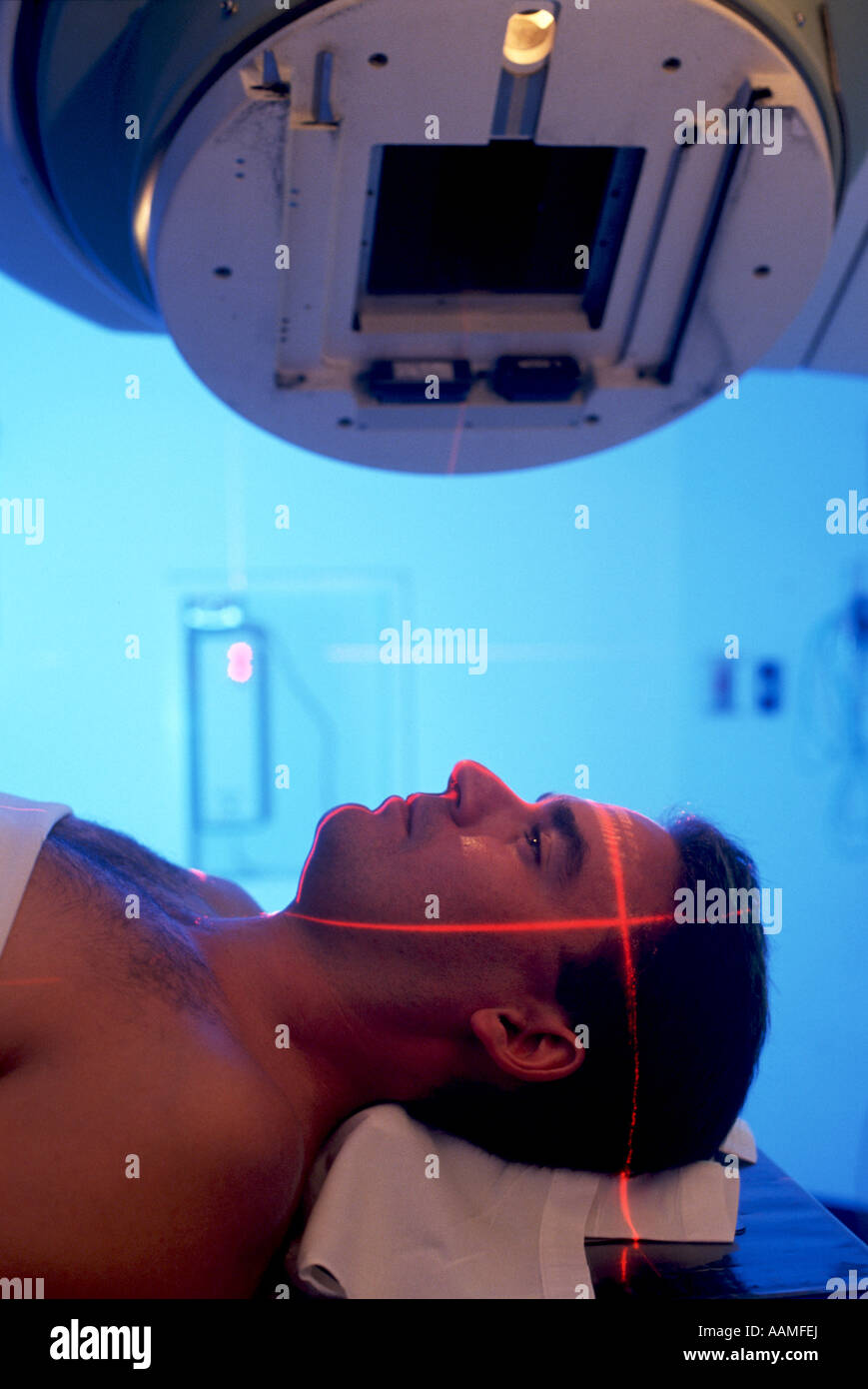 Man positioned on hospital radiation therapy machine - Stock Image